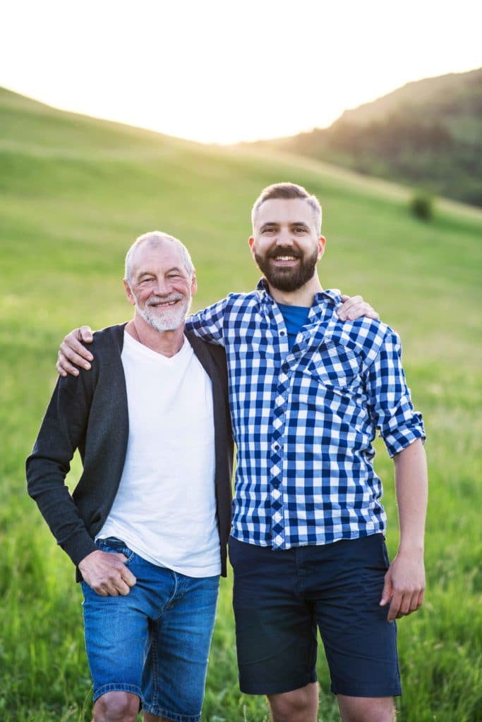 A portrait of an adult hipster son with senior father in nature at sunset.