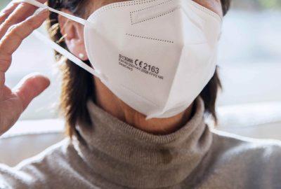 Corona Schutzmaske / FFP2 Atemschutzmaske / Frau / Maske aufsetzen